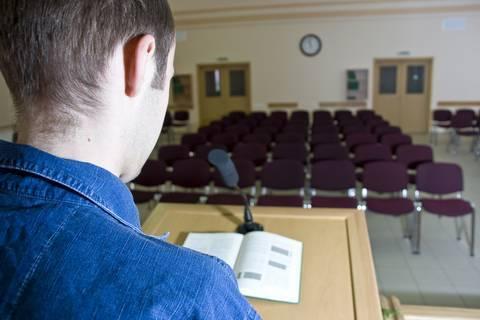 man speaking empty audience